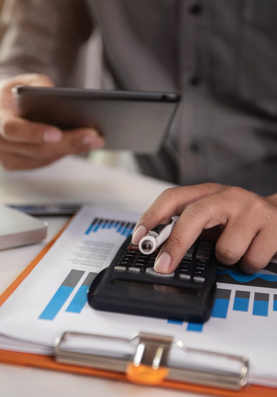 Businessman or accountant working on laptop computer and tablet with business document